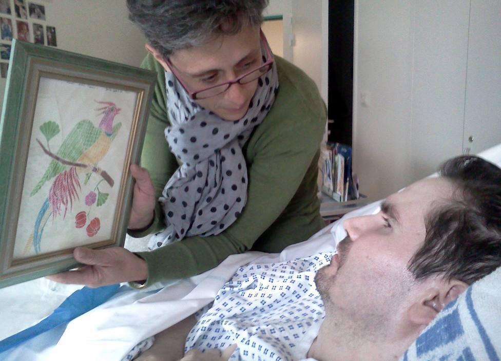 Viviane Lambert muestra un dibujo a su hijo Vincent, en la cama del hospital de Reims, Francia