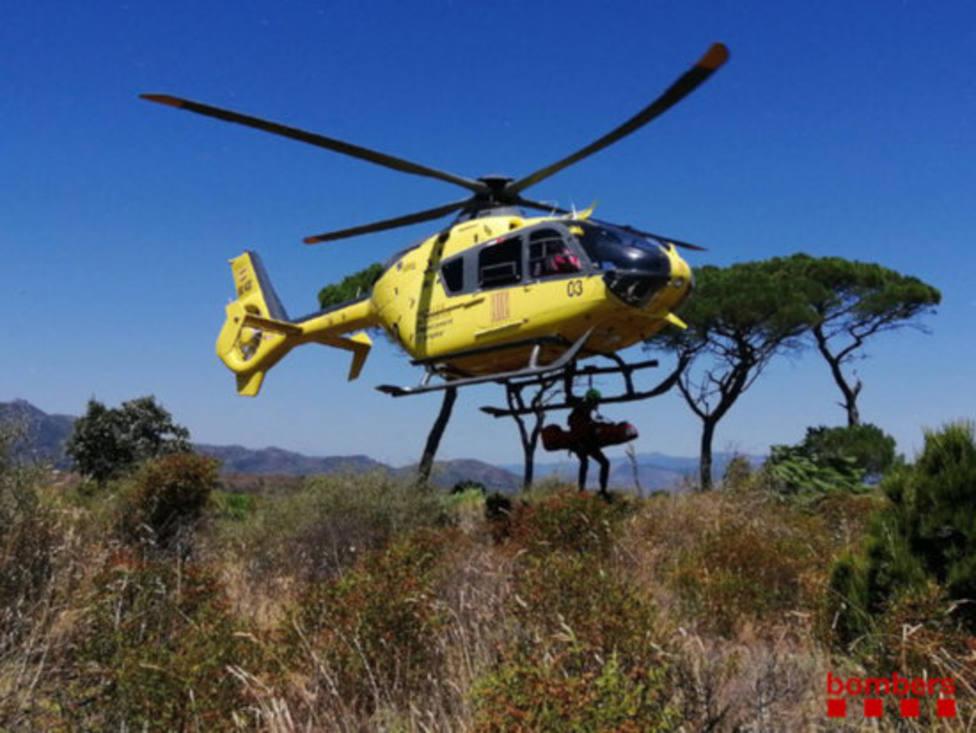 Bomberos de los GRAE cargando una camilla al helicóptero