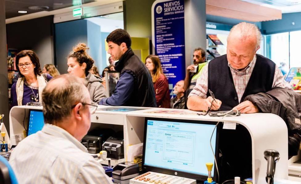 Ciudadanos depositando su voto en una oficina de correos