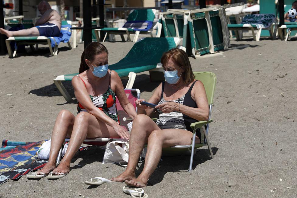 Foto de archivo de dos mujeres en la playa con mascarilla - FOTO: Europa Press / Alex Zea