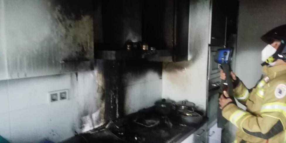 Un bombero utiliza una cámara térmica en la concina incendiada para detectar posibles focos - FOTO: Cedida