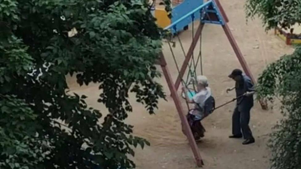 La pareja de ancianos columpiándose en el parque