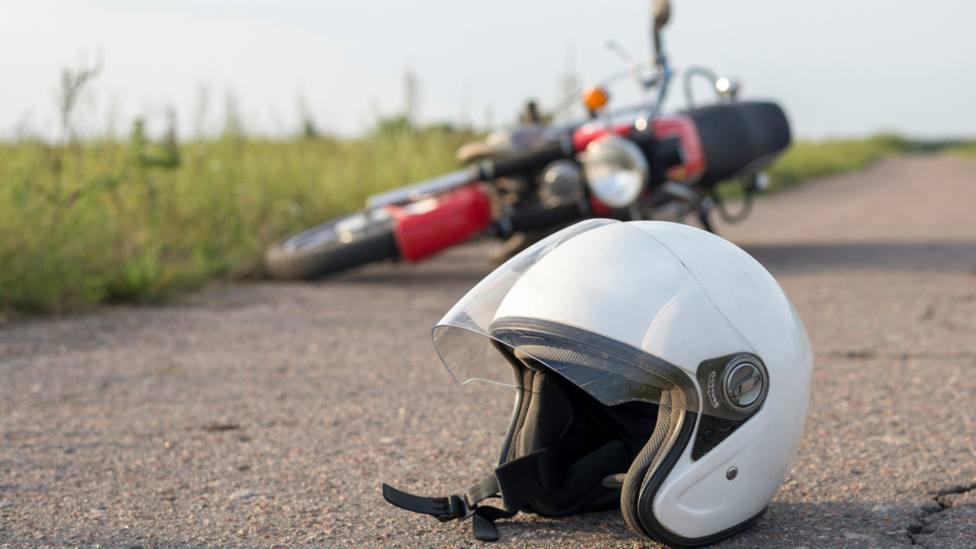 Foto de archivo de una moto tirada en la carretera y un casco