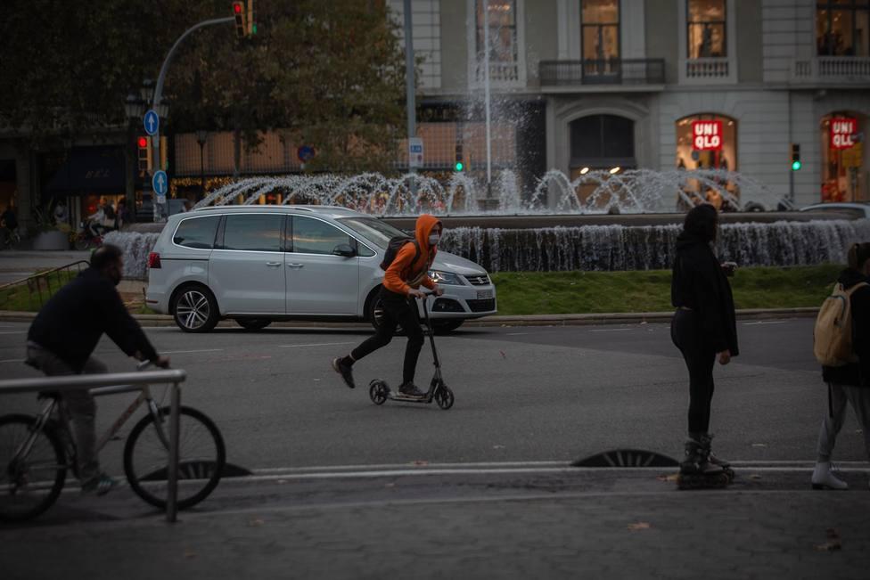 Un hombre en bici y un joven en patinete en Barcelona - David Zorrakino - Europa Press - Archivo