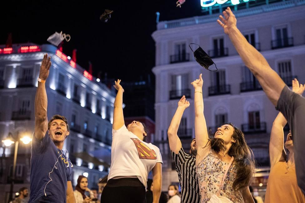 Varias personas celebran el fin del uso obligatorio de la mascarilla en espacios abiertos en la Puerta del So