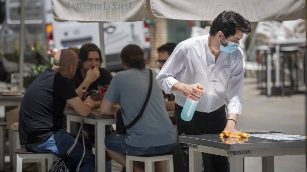 Camarero limpiando las mesas en un velador. Agencias