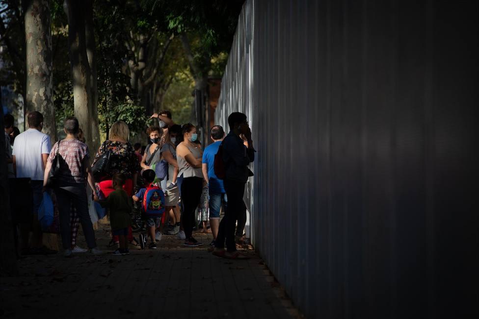 Padres y alumnos esperan a las puertas de un colegio durante el primer día del curso escolar 2020-2021