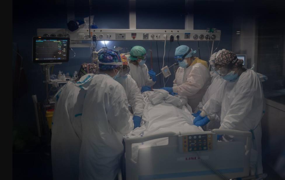 Trabajadores sanitarios protegidos atienden a un paciente en la UCI - David Zorrakino