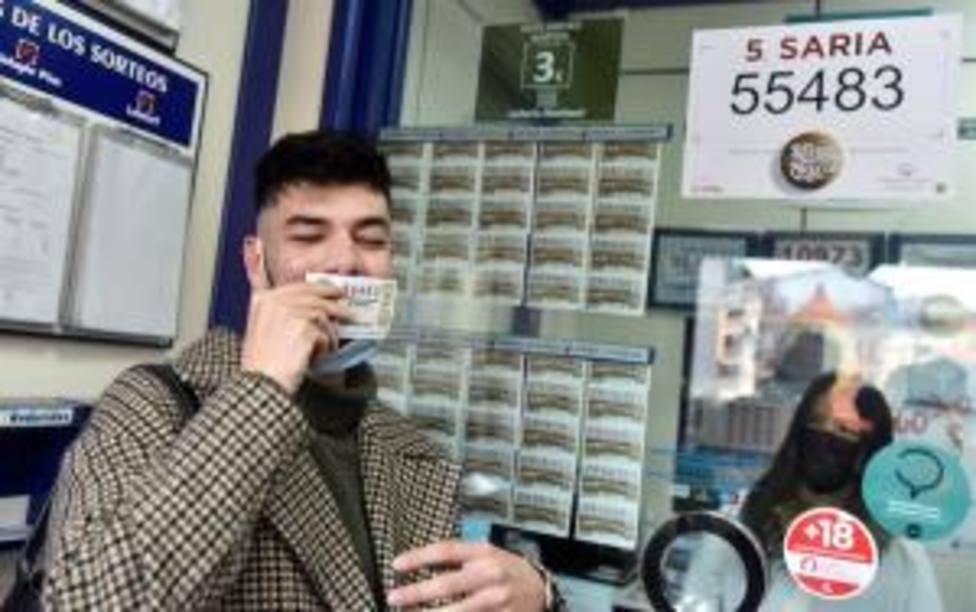 Un cliente celebra el quinto premio de la Lotería de Navidad con los dueños de la Administración de Loterías