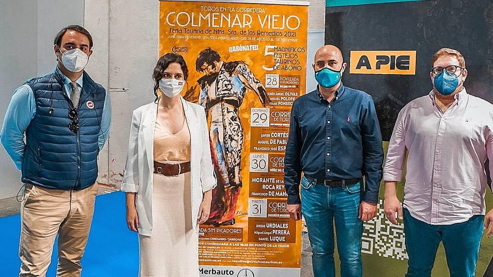 Isabel Díaz Ayuso junto a los carteles de la Feria de Colmenar Viejo presentados en FITUR