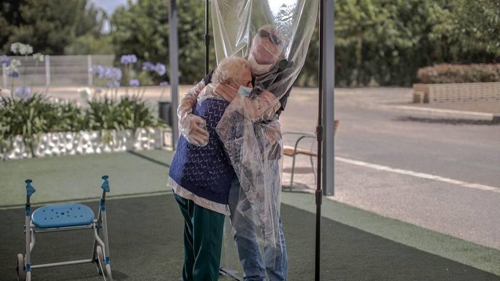 Una interna en una residencia de mayores abraza a su familiar a través de un plástico
