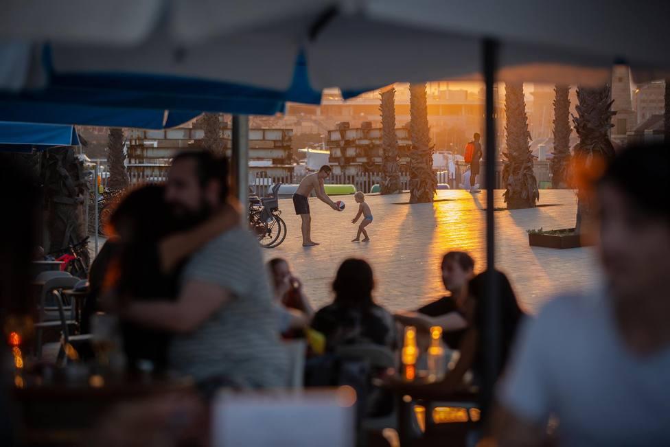 Personas en terrazas en Barcelona, Catalunya (España), a 28 de julio de 2020. Al fondo, un hombre le da un bal