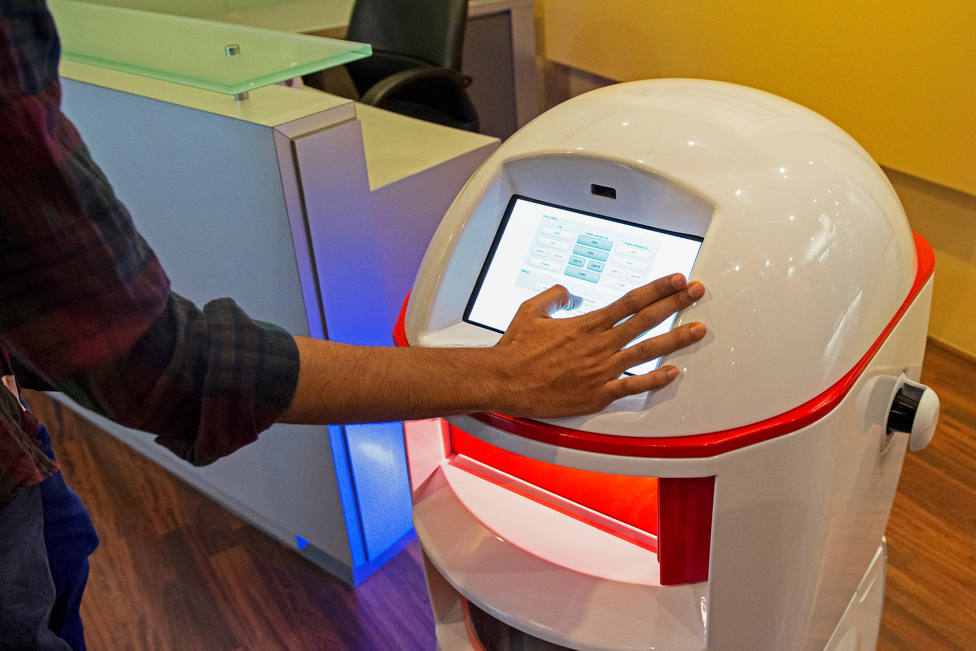 An employee of service robotics manufacturer Techmetics configures settings on the touch screen panel of the Techi Butler at their office in Singapore
