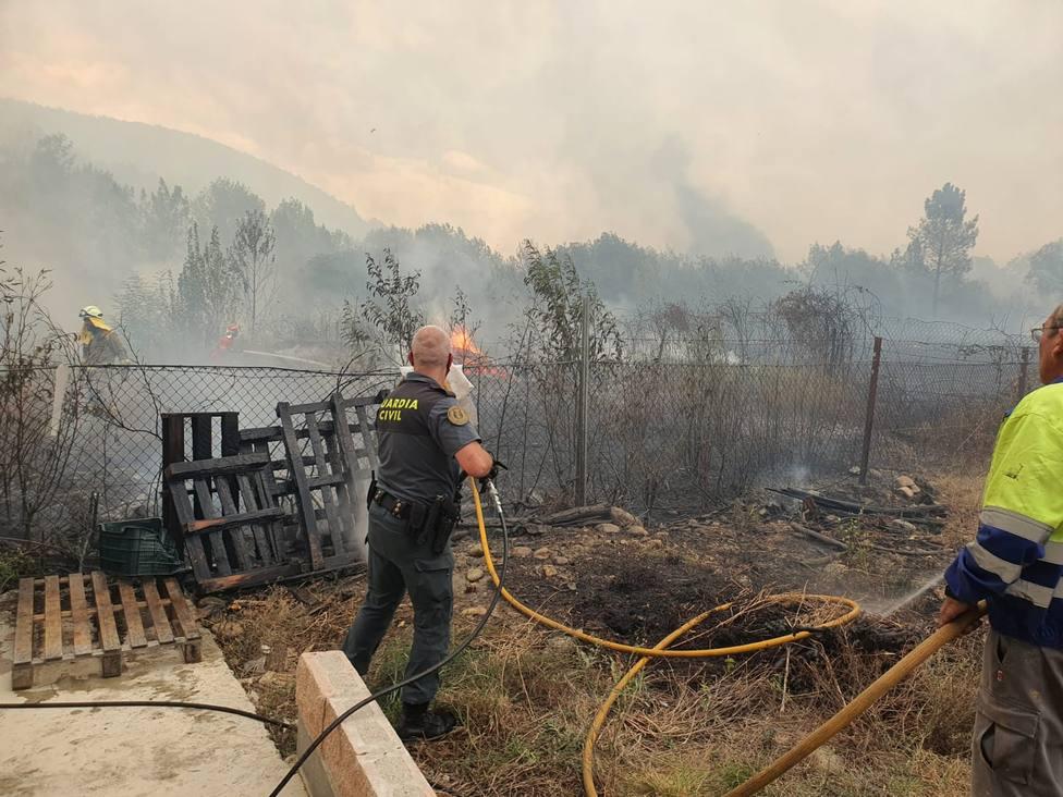 Un guardia civil colabora en los trabajos de extinción ante la proximidad del fuego a las casas