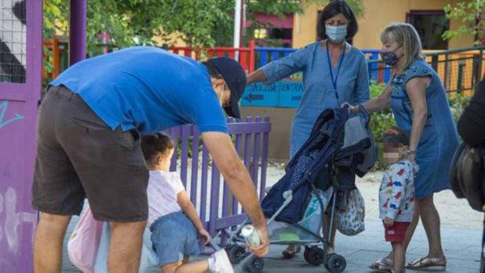 Padres desinfectando el calzado de los alumnos, a la entrada de la guardería.