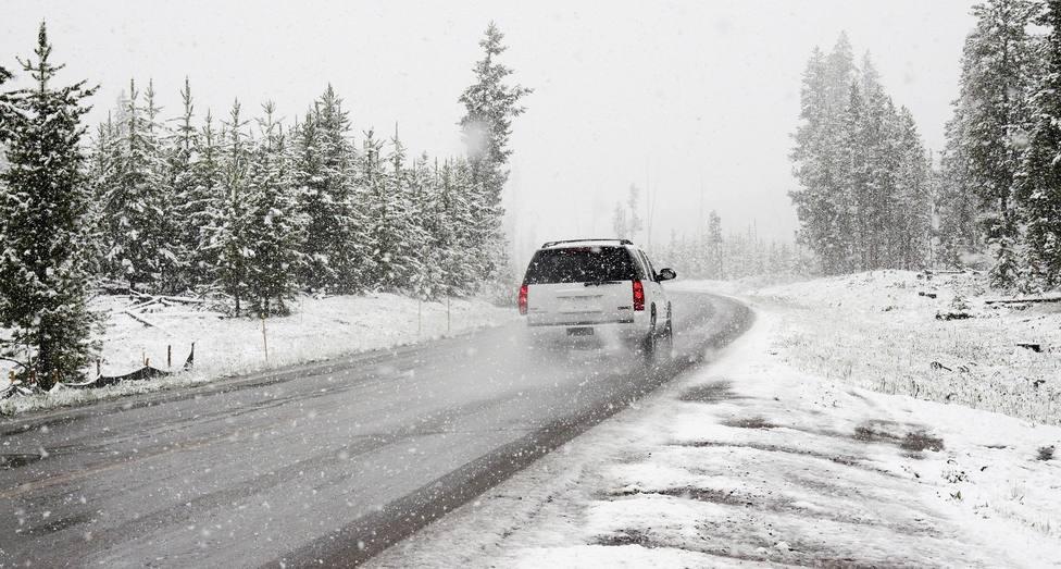 Un coche circula por una carretera nevada