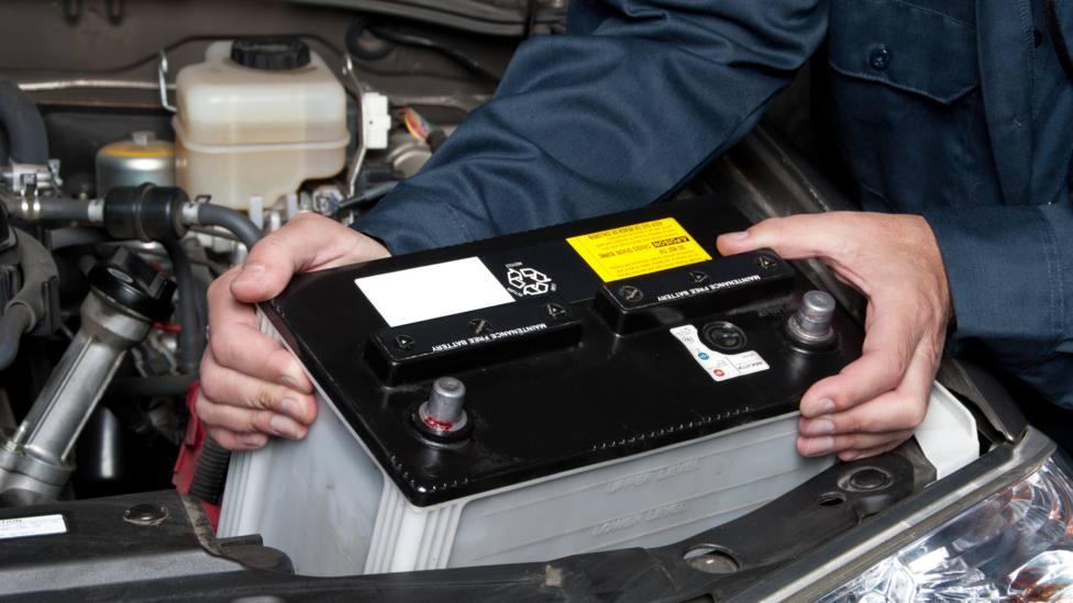 Un profesional de la mecánica sustituye una batería de un vehículo