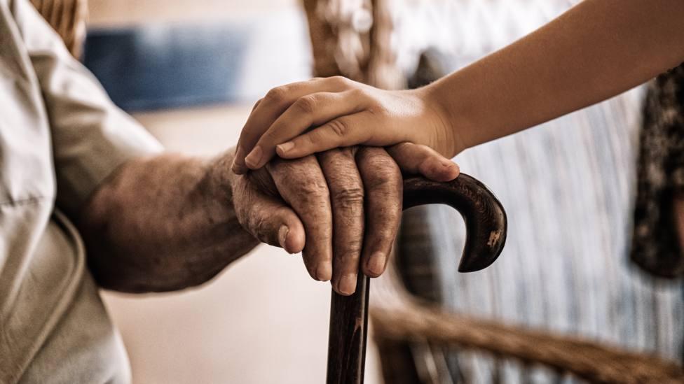 Foto de archvio de una persona mayor siendo ayuda por una profesional