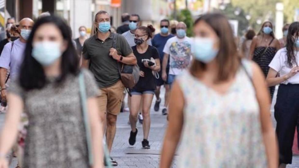 Gente con mascarilla por la calle. EFE