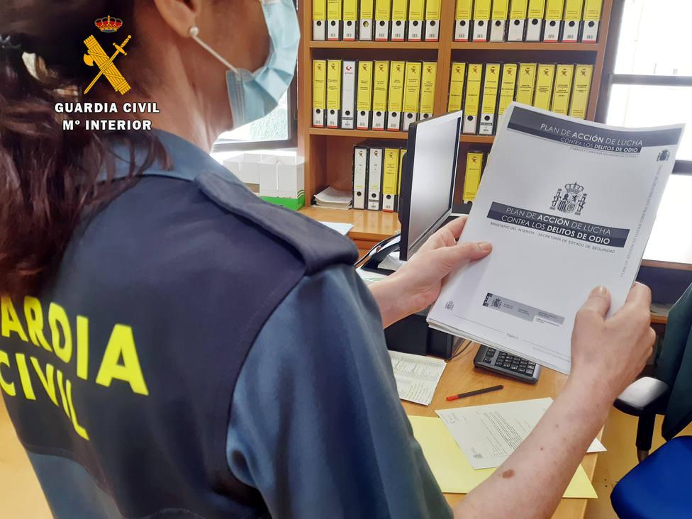 Agente de la Guardia Civil sosteniendo el Plan de Acción de Lucha contra los Delitos de Odio