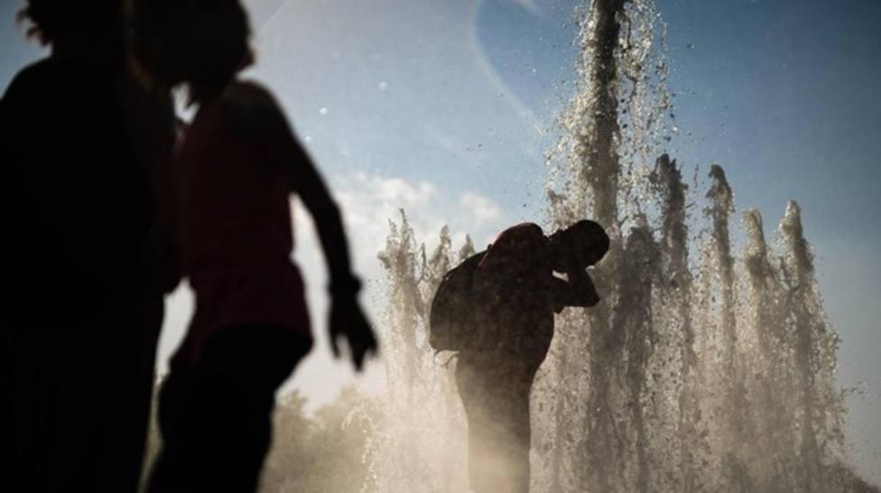 Varias personas se refrescan en una fuente para sofocar la ola de calor - Efe