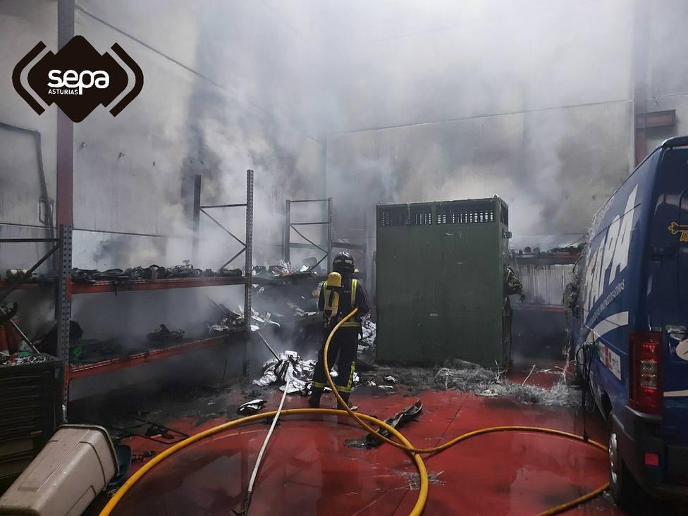 Bomberos sofocando el fuego en el interior de una nave en Parres