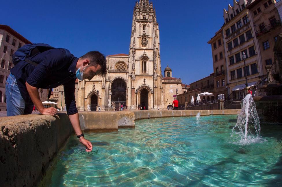Un turista se refresca en la fuente de la catedral de Oviedo