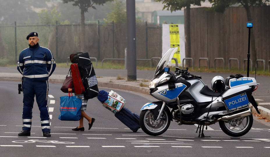 A woman carries her belongings past a police officer as some 60,000 people in Germanys financial capital are about to evacuate the city while experts defuse an unexploded British World War Two bomb found in Frankfurt