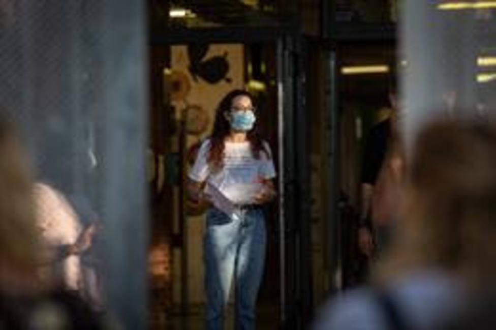 Una profesora con mascarilla a las puertas de un colegio