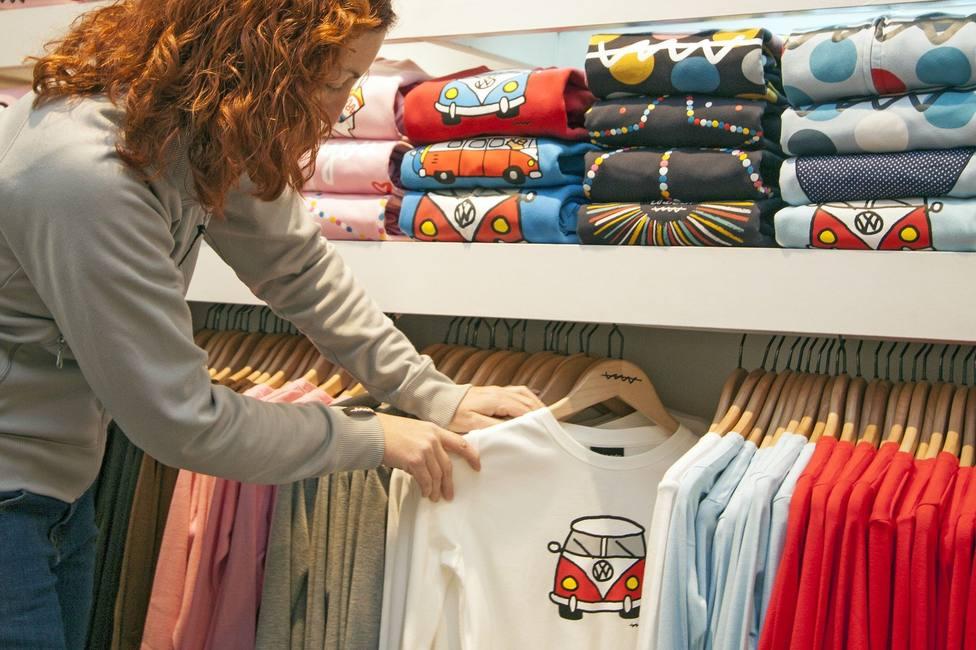 Dependienta colocando ropa en una tienda.