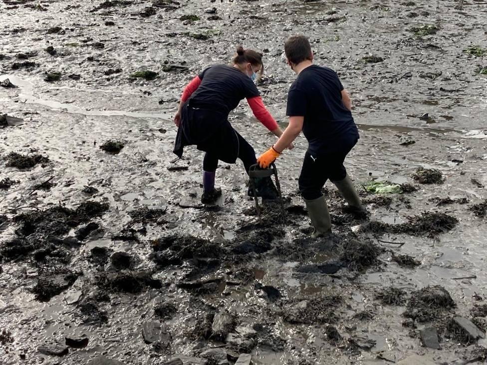 Dos de los participantes en la propuesta retirando residuos en la zona de ribera - FOTO: BNG