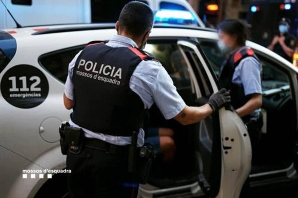 Mossos dEsquadra llevando a cabo una detención en su coche patrulla