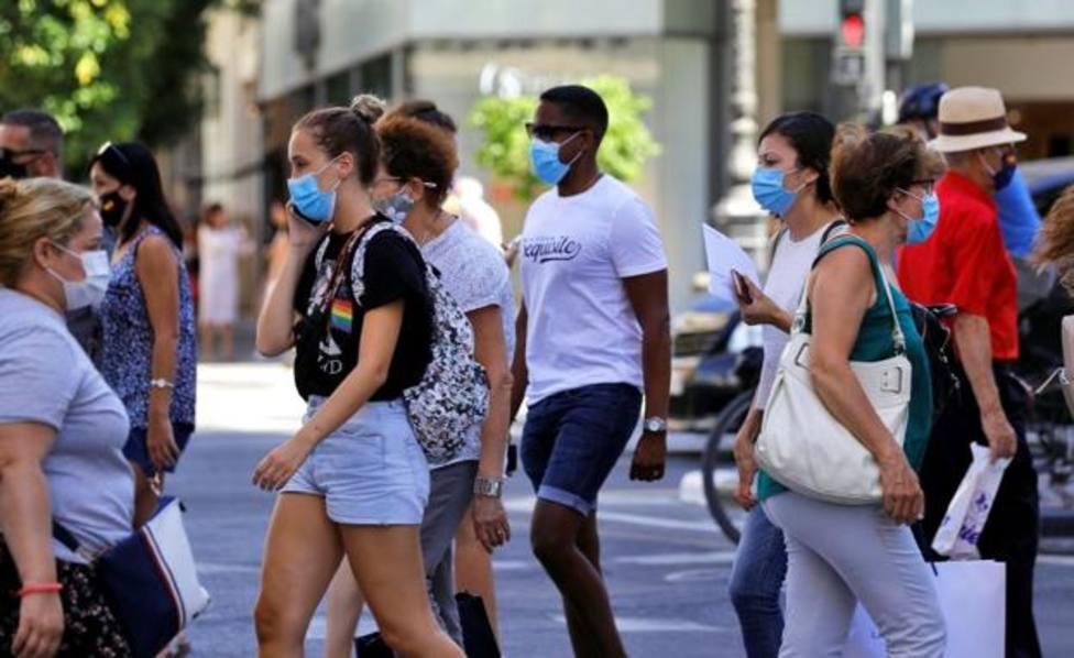 Gente por la calle con mascarillas. Agencia EFE