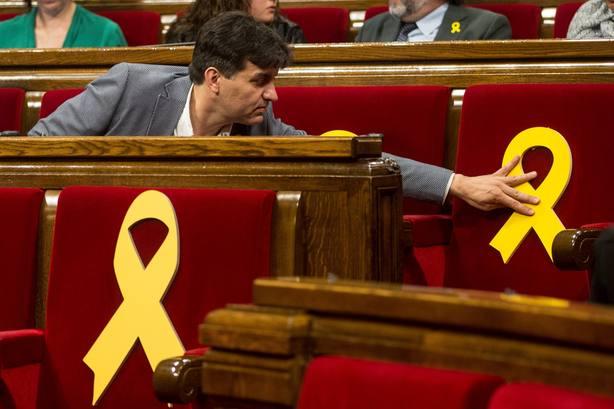 Sergi Sabrià (ERC) coloca un lazo amarillo en uno de los escaños vacios del Parlament. EFE