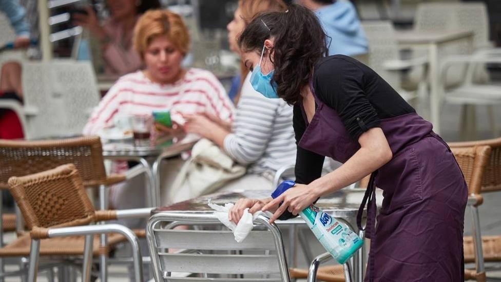 Una trabajadora desinfectando las mesas y sillas de una terraza
