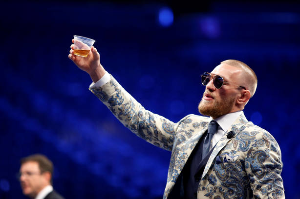 UFC lightweight champion Conor McGregor of Ireland raises a cup of Irish whiskey during post-fight news conference at T-Mobile Arena in Las Vegas