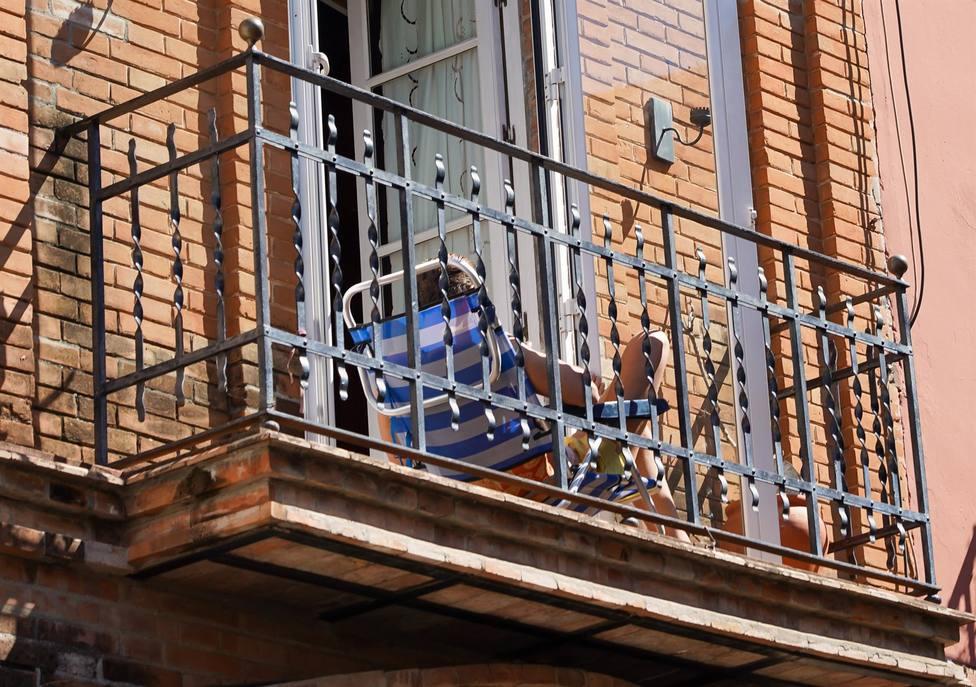 Un joven aprovecha su minúsculo balcón para tomar el sol en la tercera semana de confinamiento