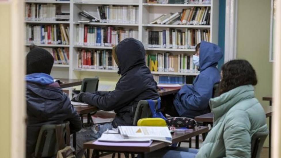 Alumnos en un aula abrigados ppr el frío