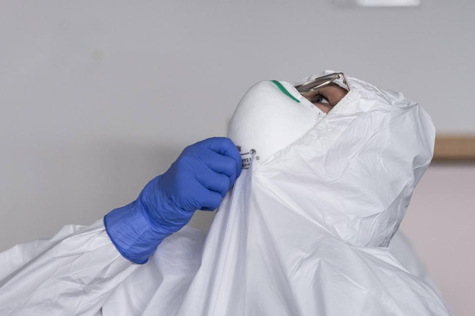 Un sanitario se ajusta su equipo de protección indivual - FOTO: Europa Press / Marco Alpozzi
