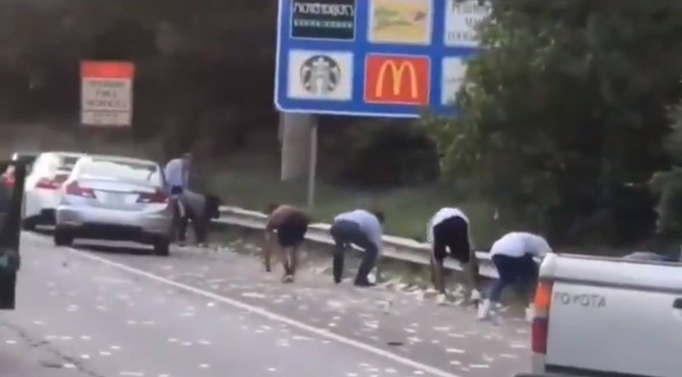 Una carretera colapsa cuando 175.000 dólares caen de un furgón y todos se pararan a recogerlos
