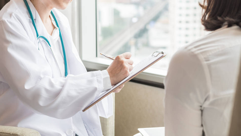 Doctor (gynecologist or psychiatrist) consulting and examining woman patients health in medical clinic or hospital health service center