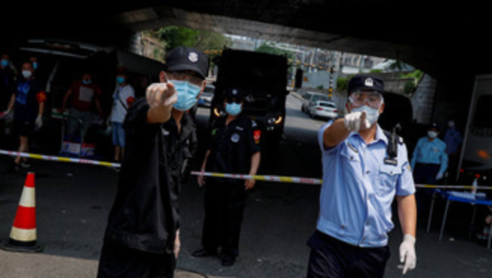 Police and security personnel attempt to prevent the photographer from taking pictures at the barrier near the Xinfadi market that has been placed under lockdown after a new outbreak of the coronavirus disease (COVID-19) in Beijing