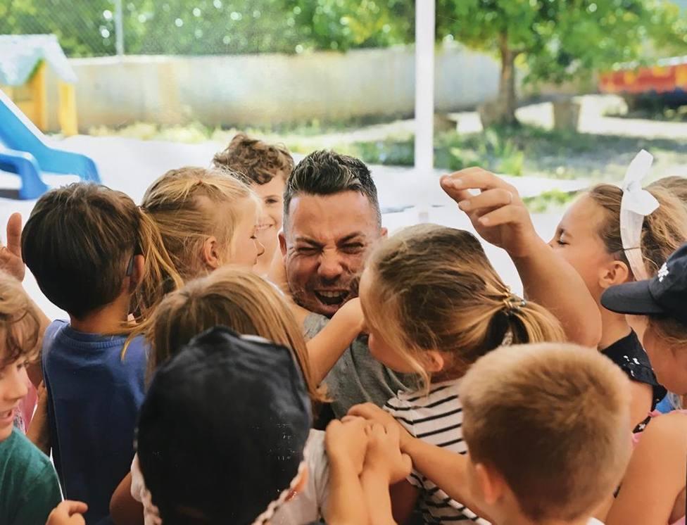 Víctor Coll recibiendo el cariño de niños