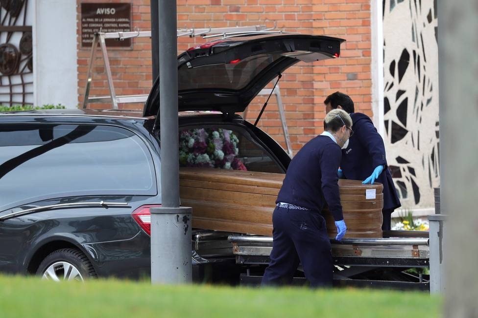 Trabajadores de una funeraria introduciendo un féretro en el vehículo