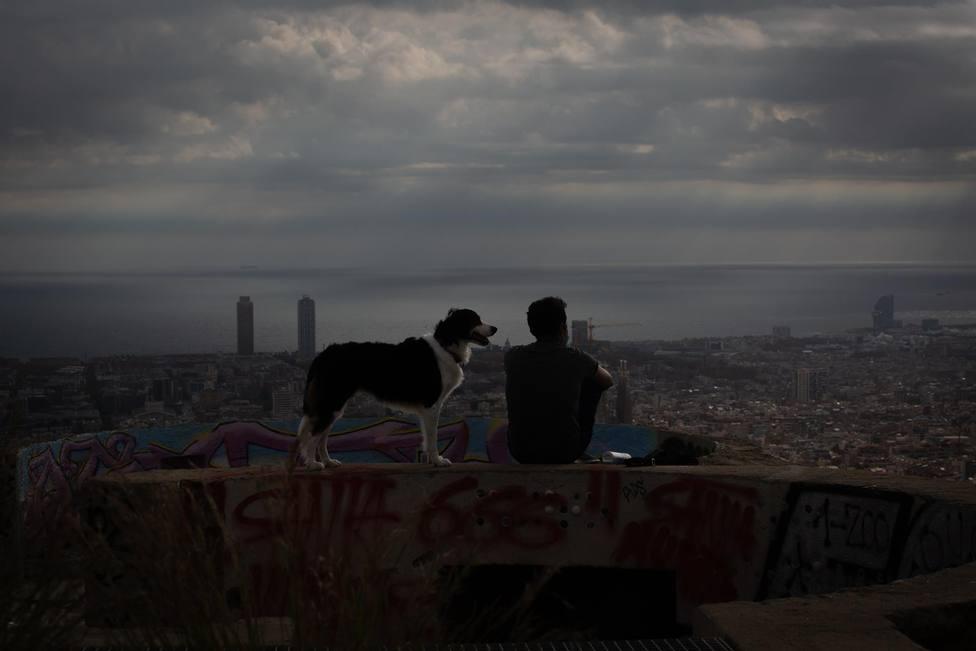 Un joven mira el paisaje en el mirador Turó de la Rovira, en Barcelona