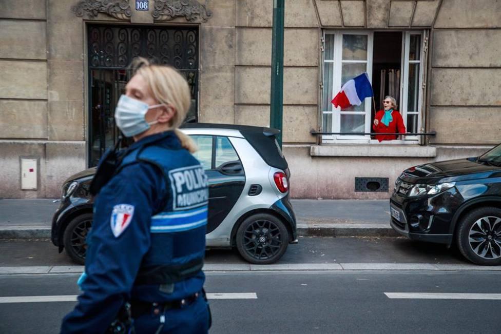 Una ciudadana francesa ondea la bandera de su país delante de una agente de Policía