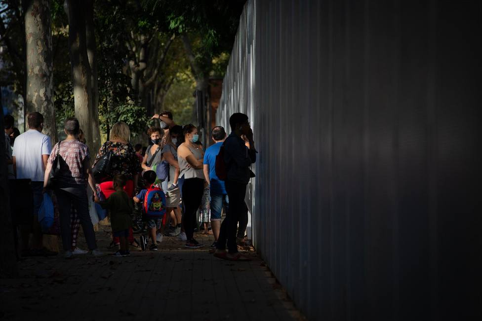 Padres y alumnos esperan a las puertas de un colegio en Barcelona