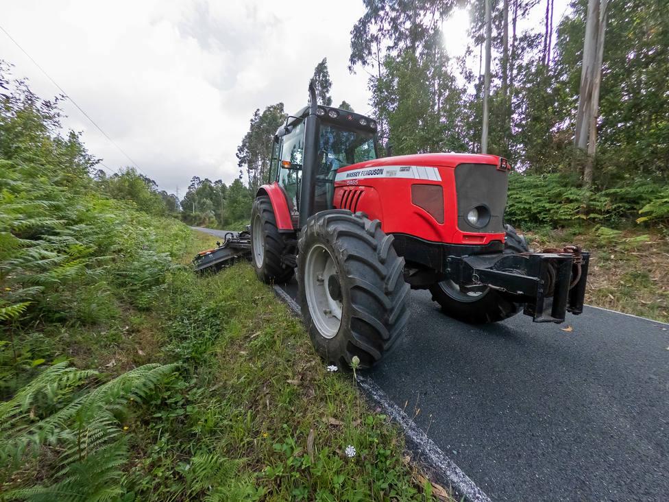 Uno de los tractores municipales rozando una pista en el lugar de Portela. FOTO: César Galdo
