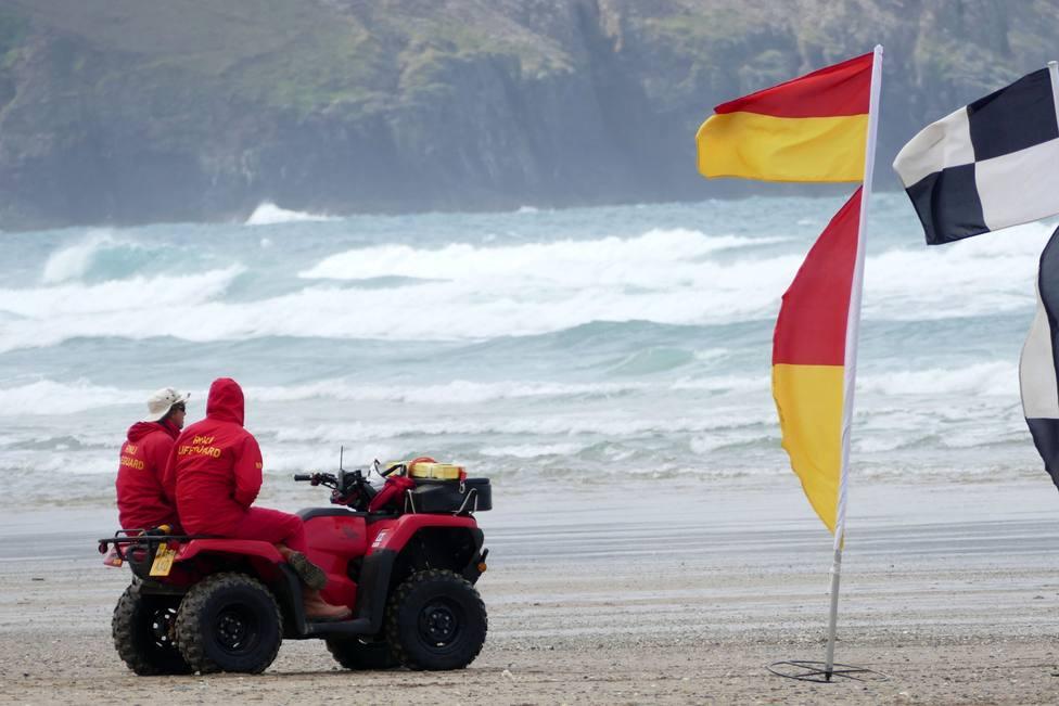 Foto de archivo de dos socorristas contemplando el mar