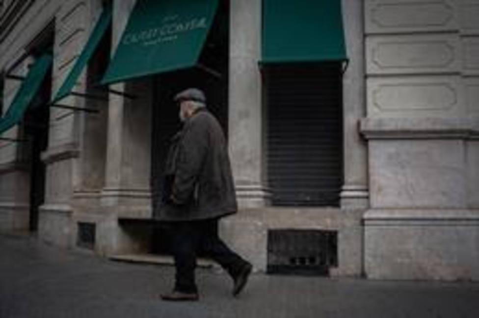 Un hombre pasa junto a un restaurante cerrado